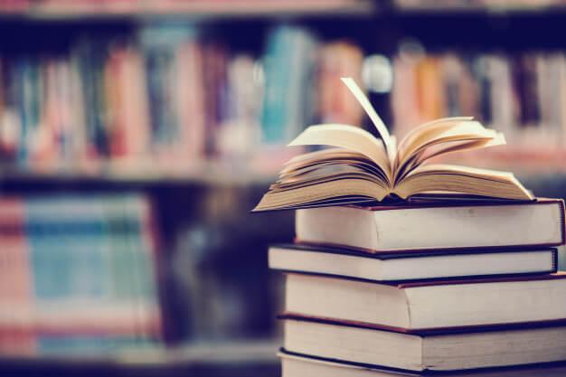 livros ao fundo e um livro aberto com as páginas para cima